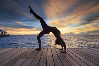 Maldives, South Ari Atoll, Thudufushi Island, Diamonds Thudufushi Resort, woman practising Yoga at  by Michele Falzone