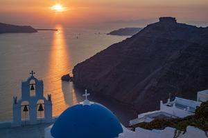 Blue dome church and famous three bells with cross and steeple in Fira, Santorini, Greece. by Michele Niles