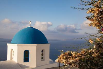 Blue domed Greek Orthodox church with bougainvillea flowers in Oia, Santorini, Greece.