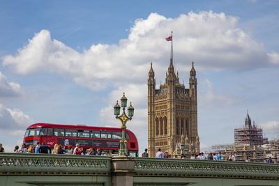 Classic double decker tour bus in London, England crossing the bridge River Thames