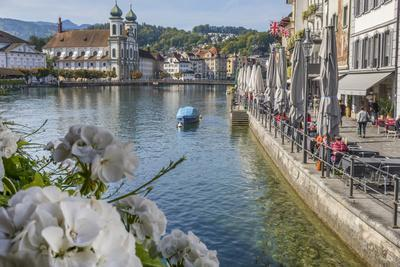 Lake Lucerne, Switzerland. Famous walking bridge and swans in river during the fall season.
