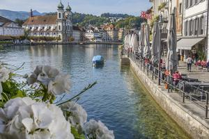 Lake Lucerne, Switzerland. Famous walking bridge and swans in river during the fall season. by Michele Niles