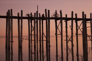 Monk walking at sunrise over the lake near wooden footbridge. Taungthaman Lake, Myanmar. by Michele Niles