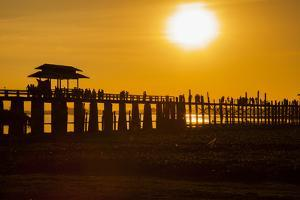 Sunset over the lake near wooden footbridge, Myanmar. by Michele Niles