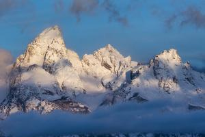 A Clearing Winter Storm Exposes Three Teton Peaks From Fog Above Jackson Hole, Wyoming by Mike Cavaroc