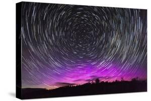 Stars Swirl around Polaris as Northern Lights Dance on the Horizon over Jackson Hole, Wyoming by Mike Cavaroc