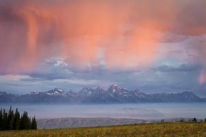 Sunrise Illuminates a Rain Shower Above a Smoke-Covered Jackson Hole, Wyoming by Mike Cavaroc