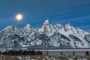 The Full Moon Sets Above The Teton Mountains And Jackson Hole, Wyoming by Mike Cavaroc