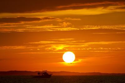 A Boat Silhouetted by a Blazing Hot, Fiery, Hellish But Gorgeous Sunset by Mike Theiss