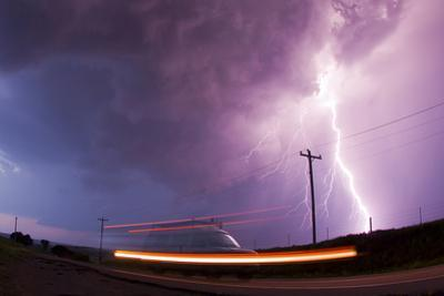 A Large Lightning Bolt Strikes Behind a Storm Chaser's Moving Van by Mike Theiss