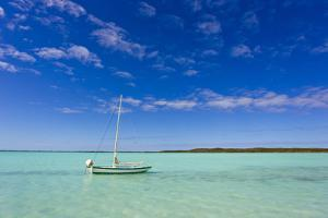 A Lone Sailboat Anchored in Turquoise Water by Mike Theiss