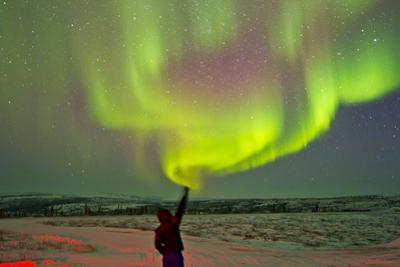 A Man Reaches for the Aurora Borealis in the Arctic Circle by Mike Theiss
