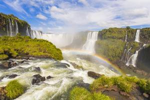 A Rainbow at Iguazu Waterfalls on the Border of Argentina and Brazil in South America by Mike Theiss