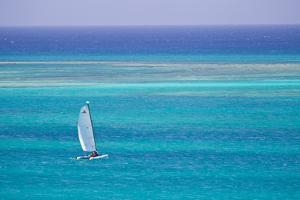 A Sailboat in the Turquoise Waters of the Caribbean Sea by Mike Theiss