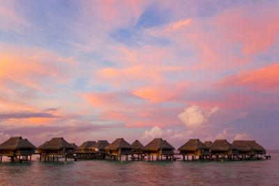 A Vibrant Pink and Red Sunset over Bungalows on Stilts over the Water by Mike Theiss