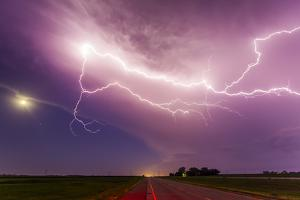 An Intense Lightning Storm over Fields and a Road in South Dakota by Mike Theiss