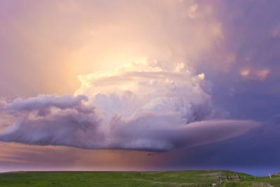 Sunset Paints a Decaying Thunderstorm and the Sky a Glowing Purple and Pink by Mike Theiss