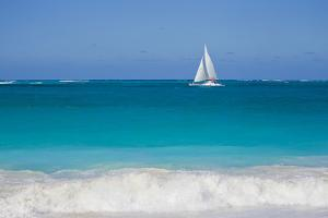 Surf Surges onto a Beach as a Sailboat Passes Offshore by Mike Theiss