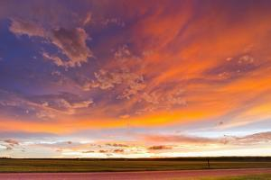 The Colorful Backside of a Thunderstorm Lit Up During Sunset by Mike Theiss