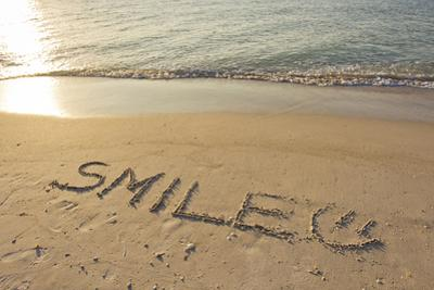 The Word Smile Written in the Sand on a Beach