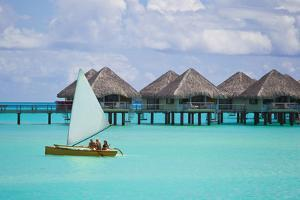 Tourists Sailing Past Bungalows on Stilts over Water in the Pacific by Mike Theiss
