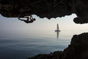 A Climber Dangles from an Overhang by Mikey Schaefer