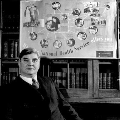 "Minister of Health Aneurin Bevan, Sitting Beneath ""National Health Service"" Poster"