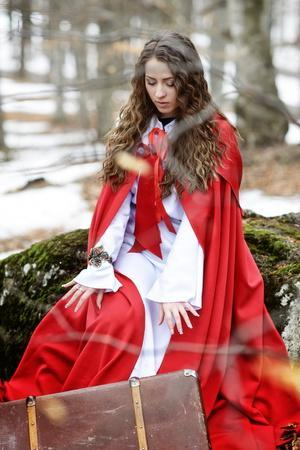Beautiful Woman with Red Cloak in the Woods