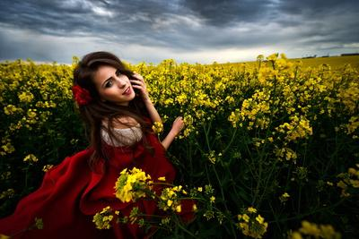 Beautiful Woman with Red Cloak on Blooming Rapeseed Field in Summer