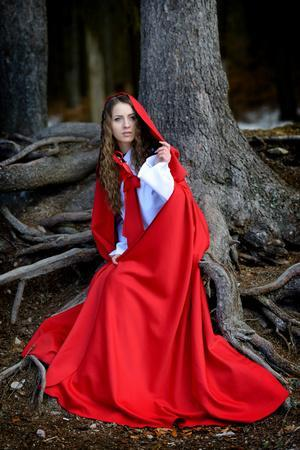 Beautiful Woman with Red Cloak Posing in the Woods