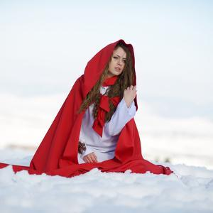 Beautiful Woman with Red Cloak Sitting on the Snow in Winter by mirceab