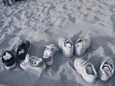 Four Pairs of Shoes on the Sand by Mitch Diamond