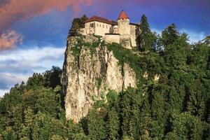 Lake Bled Castle rises on cliffs above Lake Bled, Slovenia at sunset by Miva Stock
