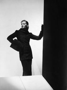 Model Wearing Cylinder-Silhouette Astrakhan Coat with Rolled Funnel Collar