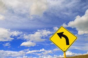 Curve Road Sign on Highway against Sky by Momatiuk - Eastcott