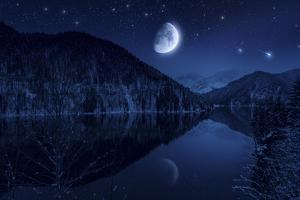 Moon Rising over Tranquil Lake in the Misty Mountains Against Starry Sky
