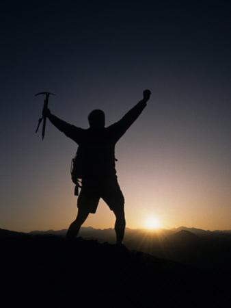 Mountain Climber Rejoices at the Summit at Sunrise