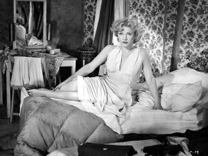Anne Baxter sitting and posed on a Bed by Movie Star News
