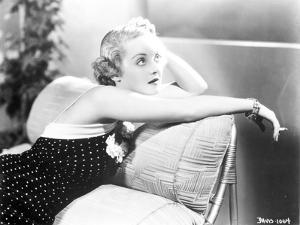 Bette Davis sitting on the Couch while Smoking a Cigarette in Black Sleeveless Polka Dot Dress by Movie Star News