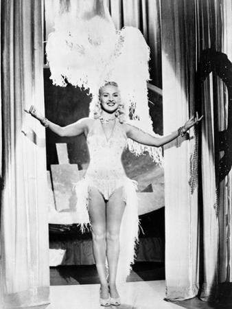 Betty Grable Posed with Hands Raised Up in Fur Headdress in White Sexy Strap Dress with Fur Bottoms by Movie Star News
