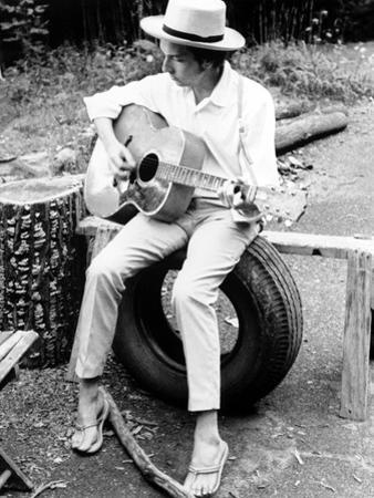 Bob Dylan Seated on Wheel Playing Guitar wearing White Long Sleeves and Slippers by Movie Star News