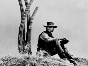 Clint Eastwood sitting in Front of Cactus, wearing Cowboy Outfit by Movie Star News