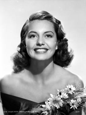 Cyd Charisse smiling in Black Dress with Flowers by Movie Star News