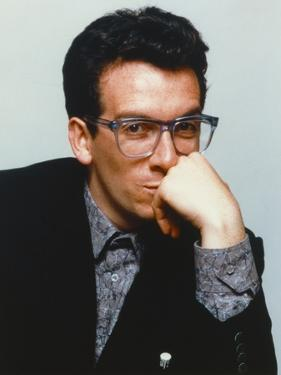 Elvis Costello Leaning Chin On Hand in Black Tuxedo by Movie Star News