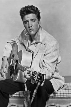 Elvis Presley Playing Guitar and Seated in Black and White by Movie Star News