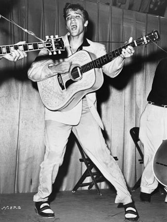 Elvis Presley singing and Playing Guitar in Coat by Movie Star News