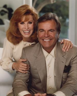 Hart To Hart Man in Suit and Woman in Long Sleeve Dress by Movie Star News