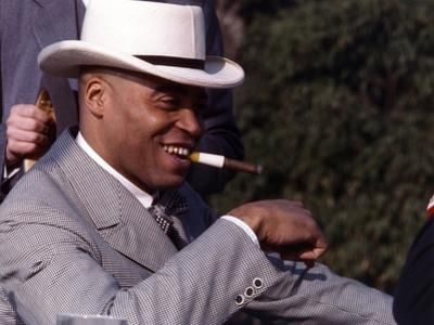 James Jones Close Up Portrait in Grey White Moire Suit and White Velvet Brimmed Hat with Cigar on t