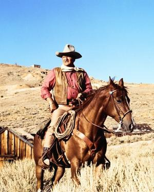 John Wayne on horse in mountains by Movie Star News