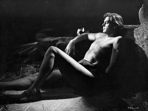 Johnny Weissmuller Lying on the Floor and Leaning on a Rock in a Classic Movie Scene by Movie Star News